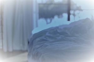 Empty messy unmade bed with white bed linen and crumpled sheets, close up view in front of a bright window